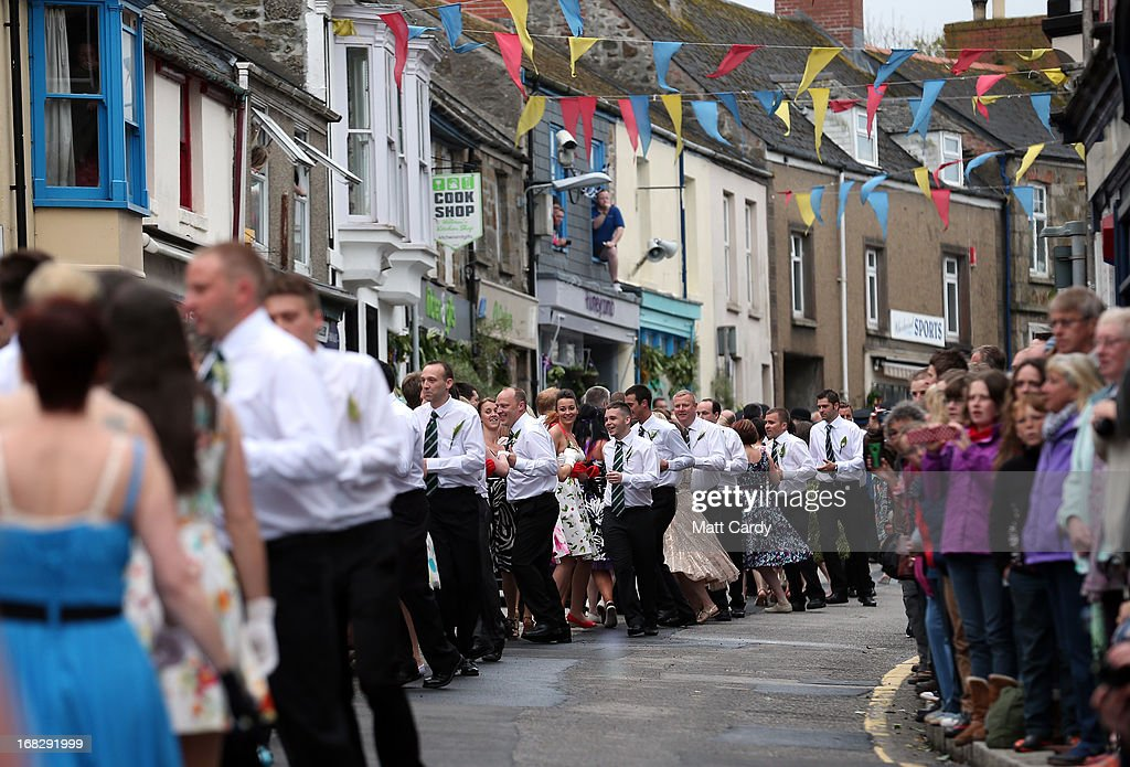 People dance through the town as they take part in the Early Morning Dance as they celebrate Helston Flora Day on May 8, 2013 in Cornwall, England. The annual Flora Dance, also known as the Furry Dance, is one of the United Kingdom's oldest customs still practised today and is said to be a celebration of the passing of Winter and the arrival of Spring. A series of dances take place throughout the day, beginning at 7am, all over the Cornish town and even in and out of private houses and shops. However the highlight is the midday dance which was traditionally the dance of the gentry in the town and is why men still wear top hats and tails while the women dance in their finest dresses.
