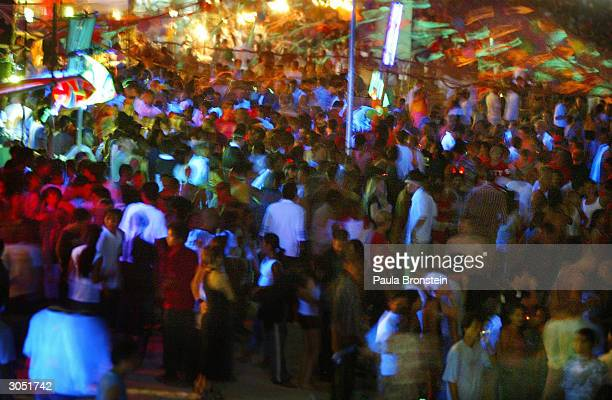 People dance to rave music on the beach March 7 2004 in Koh Phangan Thailand at the monthly 'Full Moon' party where thousands of foreigners and Thai...