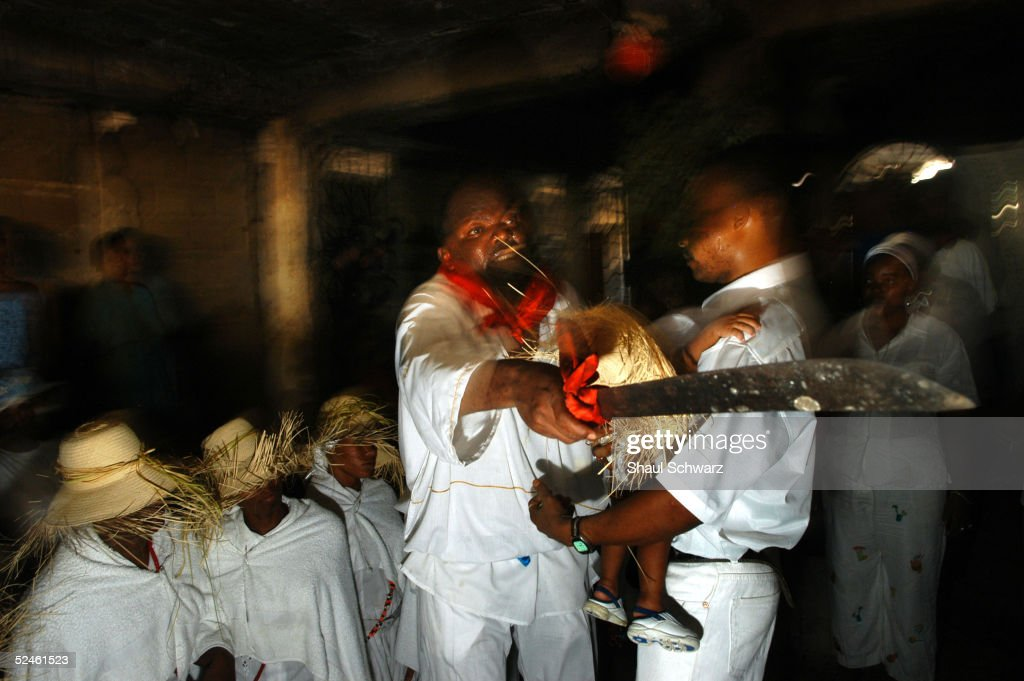 People dance to the rhythm of drums at a voodoo ceremony crowning 8 new voodoo priests March 20 2005 in PortAuPrince Haiti Voodoo is the dominant...