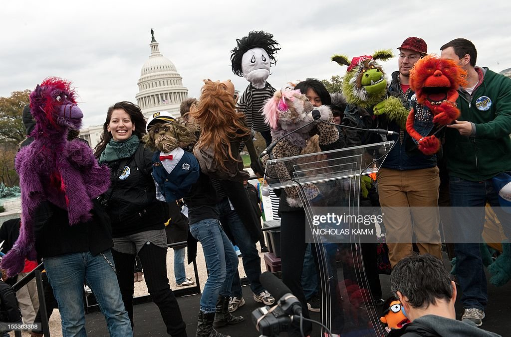 People dance with puppets in front of the US Capitol in support of public broadcasting during the'Million Puppet March' in Washington on November 3, 2012. Several hundred supporters of US public broadcasting in a good-humored protest prompted by US Republican candidate Mitt Romney's threat, in a televised debate with President Barack Obama a month ago, to halt government funding to public media if he wins the White House on ovember 6. AFP PHOTO/Nicholas KAMM