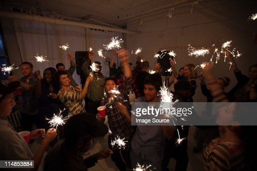 People dancing at party with sparklers : Stock Photo