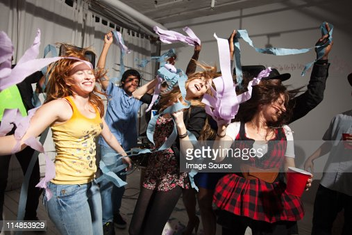 People dancing at party with streamers : Stock Photo