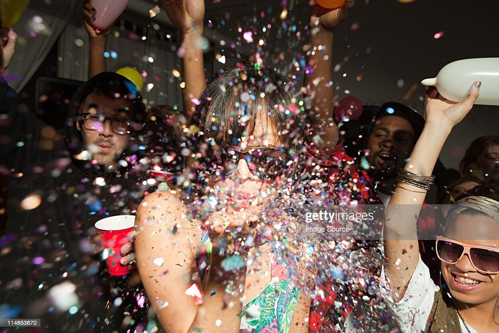 People dancing at party, woman blowing glitter