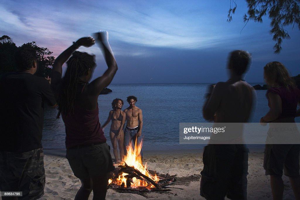 People dancing near bonfire on beach : Stock Photo