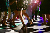 People Dancing on a block shaped dance floor at night outdoors with the focus on a girl dancing with high heals bottom half lifting the one leg Cape Town South Africa