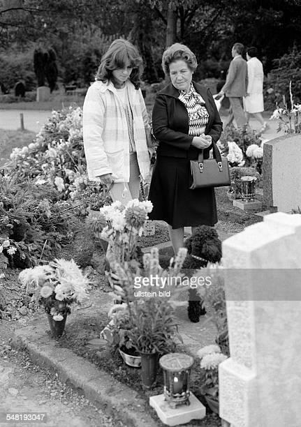people death mourning churchyard young girl and older woman stand at a tomb flowers aged 16 to 18 years aged 60 to 70 years Birgit Frieda