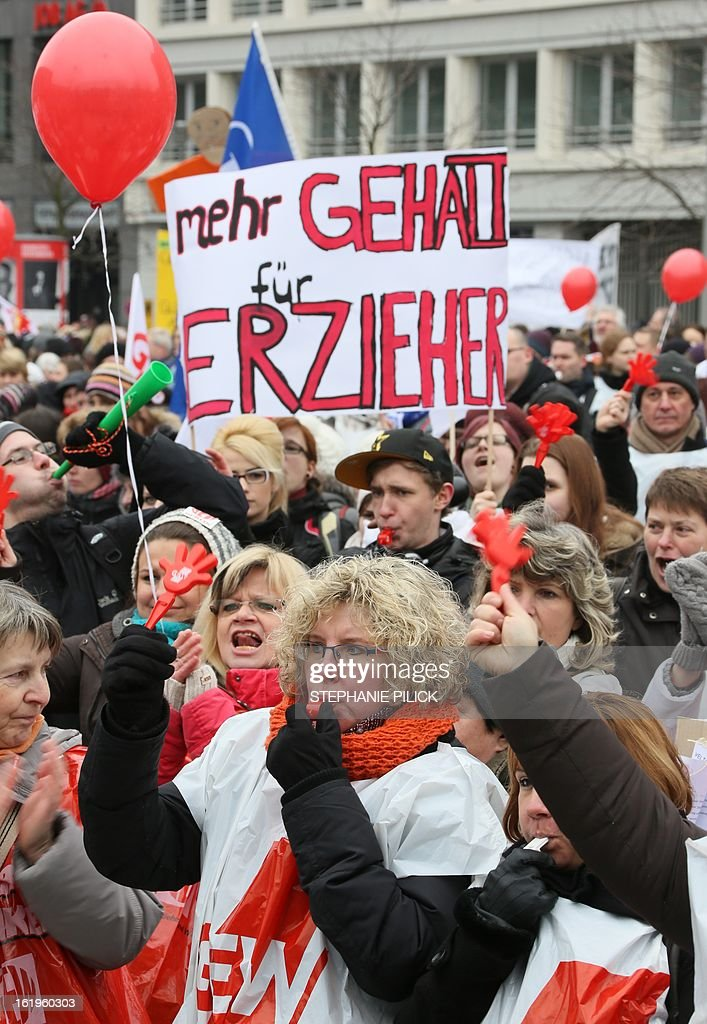 People demonstrate during a rally by the Education and Science Workers' Union (GEW) in Berlin, Germany, on February 18, 2013. Teachers and educators striked at more than 100 schools after a call from the GEW union. The warning strike is the start of a nationwide wave of strike in the civil service. The banner reads 'Better salary for the teacher'. AFP PHOTO / STEPHANIE PILICK /GERMANY OUT