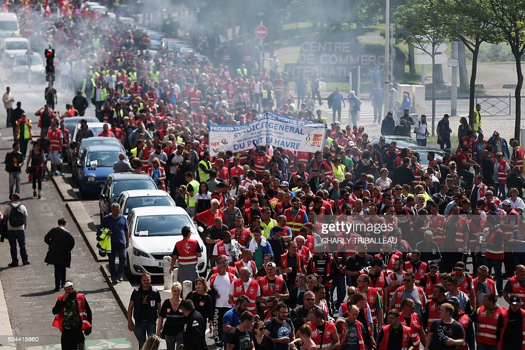 People demonstrate in Le Havre northwestern France, on May 26, 2016 to protest against the government's proposed labour reforms. Refinery workers stepped up strikes that threaten to paralyse France weeks ahead of the Euro 2016 tournament as the government moved to break their blockades, escalating a three-month tug-of-war over labour reforms. / AFP / CHARLY