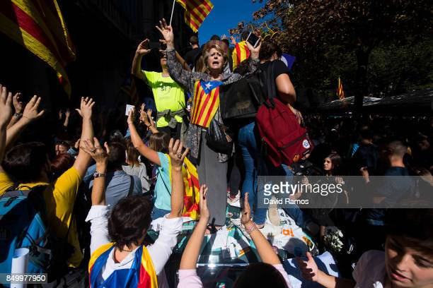 People demonstrate on a Spanish Civil Guard Police car outside the Catalan VicePresident and Economy office as police officers holds a searching...