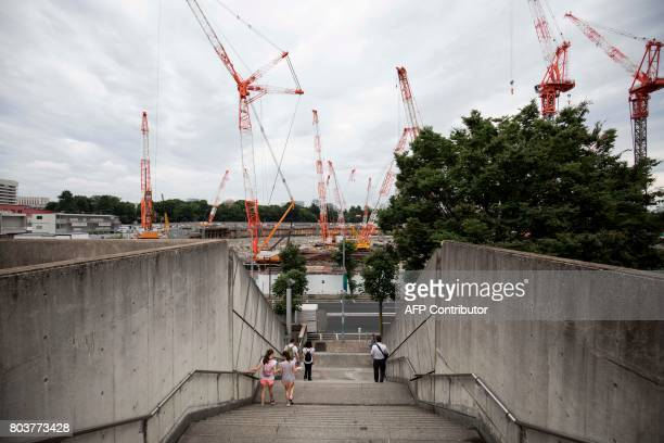 People descend stairs at the Tokyo metropolitan gymnasium as the construction site for the National Stadium venue for the upcoming Tokyo 2020...