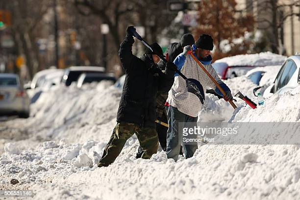People dig out cars on a sunny day following a blizzard on January 24 2016 in the Brooklyn borough of New York City The day long blizzard caused the...