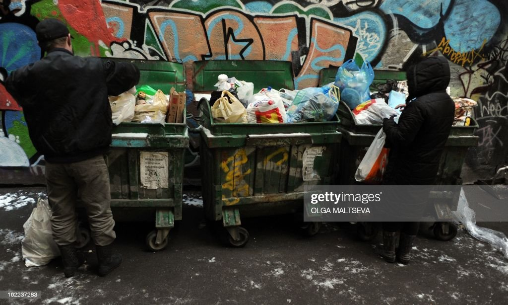 People dig through garbage in trash boxes in a courtyard in Russia's second city of St. Petersburg, on February 20, 2013.