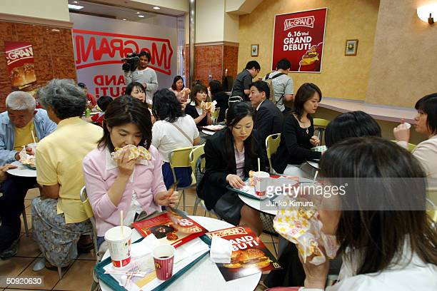 People dine at a McDonald's on June 3 2004 in Tokyo Japan McDonald's will launch a new hamburger the McGrand that uses larger beef patties on June 16...