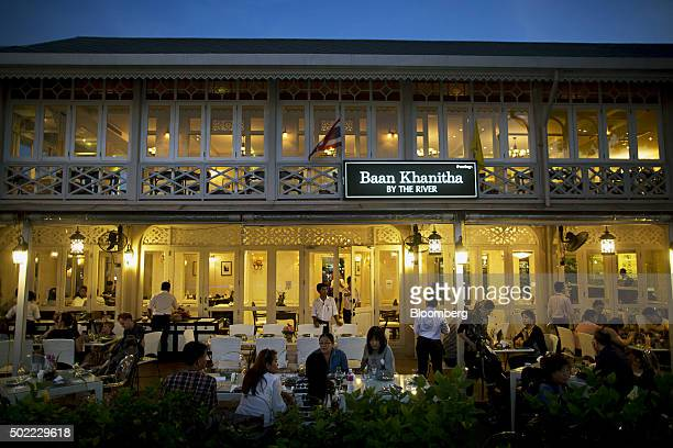 People dine at Baan Khanitha By The River restaurant at Asiatique The Riverfront openair mall in Bangkok Thailand on Friday Dec 18 2015 Thai economic...
