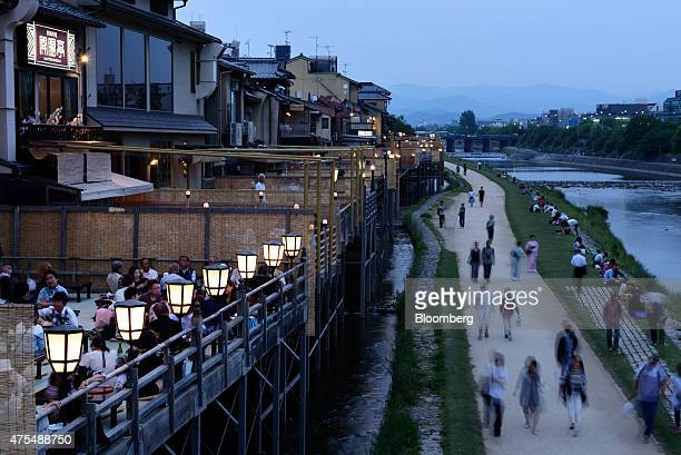 People dine at restaurants along the Kamogawa river in Kyoto Japan on Thursday May 28 2015 Spending by visitors to Japan jumped to the highest level...