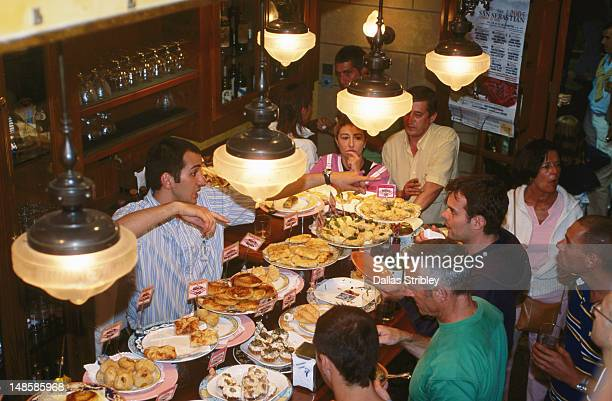 People dining at Pintxos line counter of busy 'Ormazabal Tabema' bar.