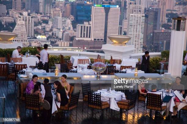 People dining at Sirocco, with city buildings beyond.