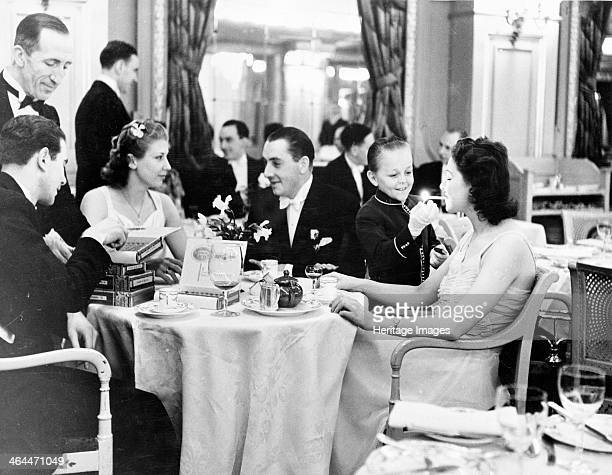 People dining at the Trocadero Restaurant Leicester Square Westminster London 1939 A young boy wearing gloves lights a woman's cigarette The elegant...
