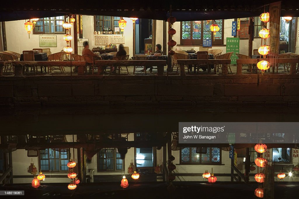 People dining by canal. : Stock Photo