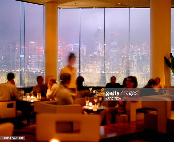 People dining in restaurant, Hong Kong skyline in background