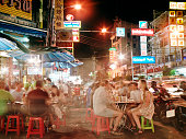 People dining outside at food stalls at night