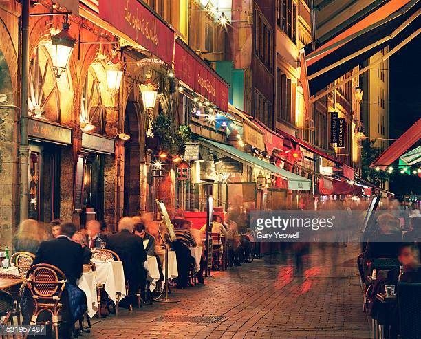 People dining outside in narrow street in Lyon