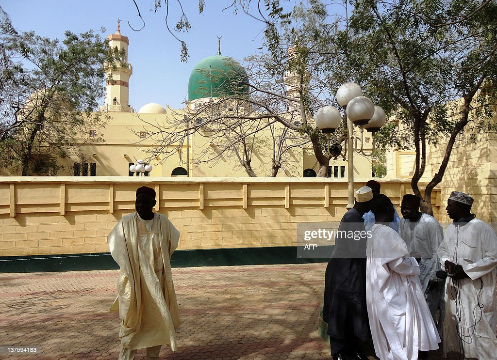 People discuss in front of the central mosque in the northern Nigerian city of Kano where around 200 muslim faithful including clerics and...