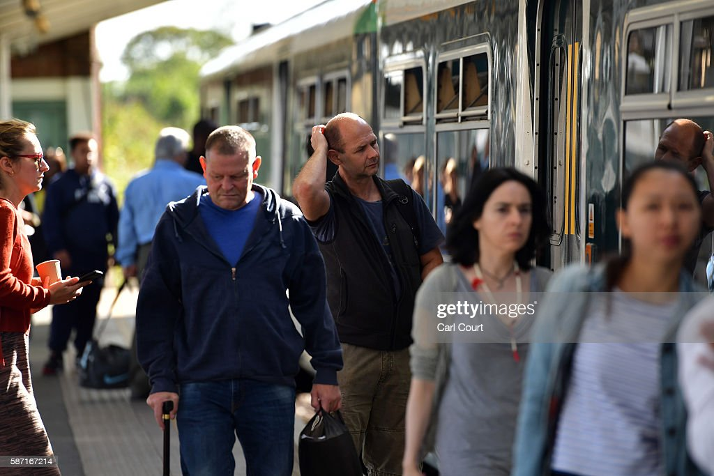 People disembark and wait to board a train on the hugelyreduced Southern rail service at Peckham Rye station on August 8 2016 in London England...