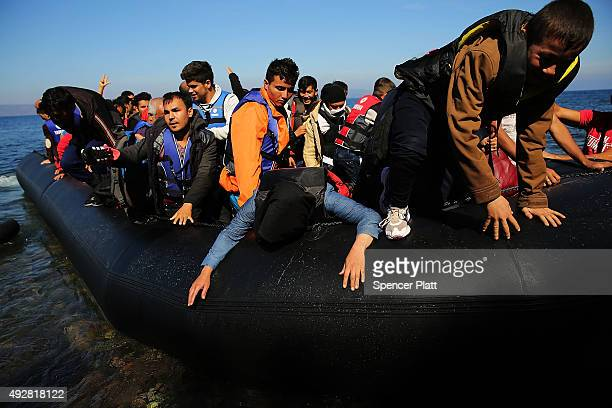 People disembark from a raft moments after arriving from Turkey on October 15 2015 in Sikaminias Greece Dozens of rafts and boats are still making...
