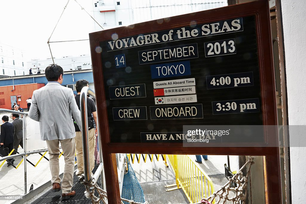 People disembark the Royal Caribbean Cruises Ltd.'s Voyager of the Seas, berthed at the Ohi wharf in Tokyo, Japan, on Saturday, Sept. 14, 2013. Royal Caribbean, the worlds second-largest cruise-line operator, doubled its dividend and will make directors stand for election every year. Photographer: Yuriko Nakao/Bloomberg via Getty Images