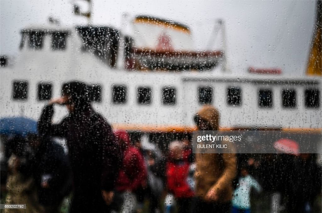 People disembark under the rain from a ferry at the Karakoy port along the western bank of the Bosphorous in Istanbul on March 14, 2017. /