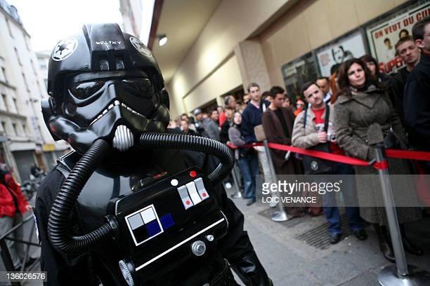 People disguised as characters of US director George Lucas films Star Wars queue in front of the Grand Rex cinema in Paris 27 October 2007 to attend...