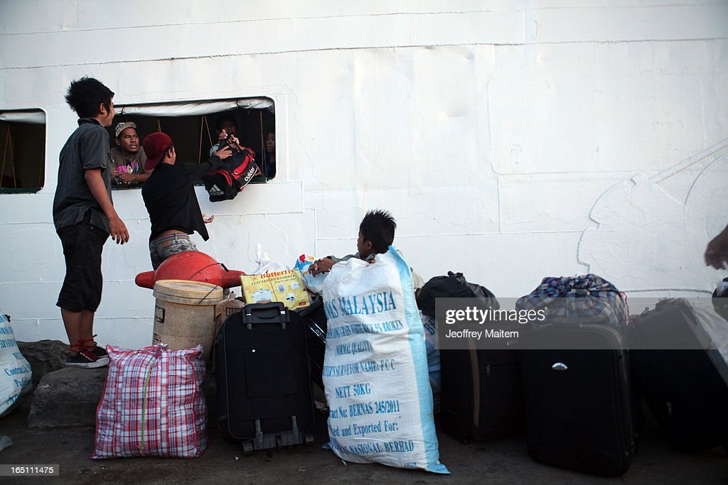 People, displaced by continuing armed conflict between the supporters of Philippine Muslim clan Sulu Sultan Jamalul Kiram III and Royal Malaysian Police in Sabah, Malaysia, arrive at Bonggao Port on March 30, 2013 in Bonggao, Tawi-Tawi, Philippines. Following the insurgency in Sabah and the Malaysian government's subsequent crackdown on undocumented Filipinos, over 4000 people, mostly Filipino Muslims, have begun evacuating to the southern provinces of Basilan, Sulu, and Tawi-Tawi in the Philippines, with numbers expected to reach more than 100,000.