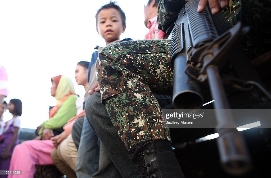 People displaced by continuing armed conflict between the supporters of Philippine Muslim clan Sulu Sultan Jamalul Kiram III and Royal Malaysian Police in Sabah, Malaysia, arrive on a military truck at Bonggao on March 30, 2013 in Bonggao, Tawi-Tawi, Philippines. Following the insurgency in Sabah and the Malaysian government's subsequent crackdown on undocumented Filipinos, over 4000 people, mostly Filipino Muslims, have begun evacuating to the southern provinces of Basilan, Sulu, and Tawi-Tawi in the Philippines, with numbers expected to reach more than 100,000.