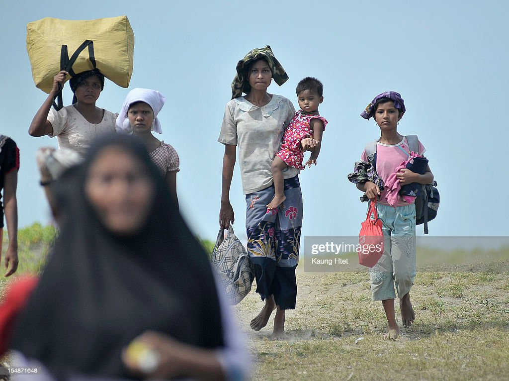 People, displaced by the recent violence between Buddhist Rakhine and Muslim Rohingya in Kyuk Phyu township, carry their belongings as they arrive to Thae Chaung refugee camp on October 28, 2012 on the outskirts of Sittwe, Myanmar. Over twenty thousand people have been left displaced following violent clashes which has so far claimed a reported 80 lives. Clashes between Rakhine people, who make up the majority of the state's population, and Muslims from the state of Rohingya began in June.