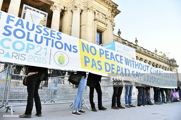 People display a banner reading which translates as 'false solutions COP21 No peace without climate justice' in front of the 'Solutions COP21'...