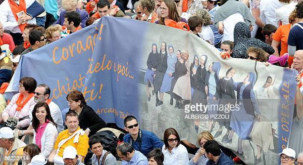 People display a banner showing nuns set in a pose and manner replicating 'Lunch atop a skyscraper ' by Charles C Ebbets during a canonization...