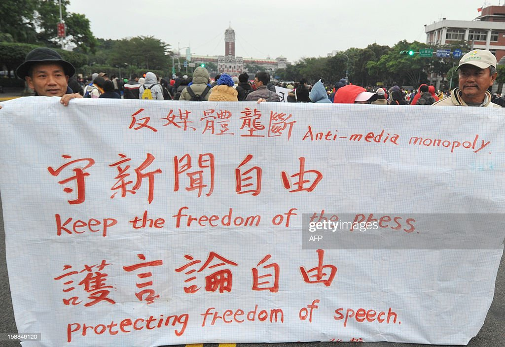 People display a protest banner calling for freedom of the press, as they attend a flag-raising ceremony on New Year's Day at the Presidential Office Square in Taipei on January 1, 2013. Student groups called on Taiwan's President Ma Ying-jeou to object to the planned sale of Hong Kong-based Next Media's Taiwan assets which they fear could create a pro-China media monopoly. AFP PHOTO / Mandy CHENG