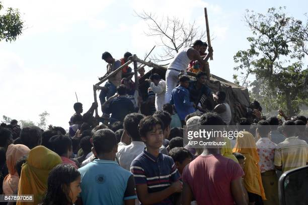 People distribute relief supplies for Rohingya Muslim refugees at Kutupalong refugee camp in the Bangladeshi locality of Ukhia on September 16 2017...