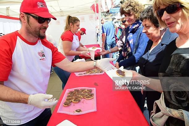 People distribute tartines of Nutella on May 17 2014 in Alba northern Italy during the celebrations of the 50th anniversary of Nutella the chocolate...