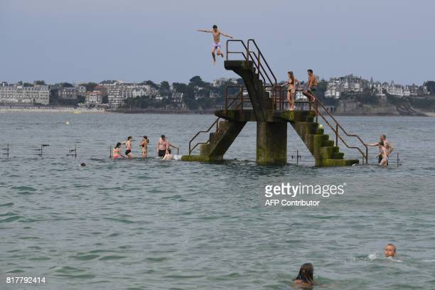 People dive into the water from a diving platform on the beach of SaintMalo western France on July 18 during a heatwave / AFP PHOTO / DAMIEN MEYER