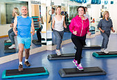 Group of senior people do exercise in a fitness club