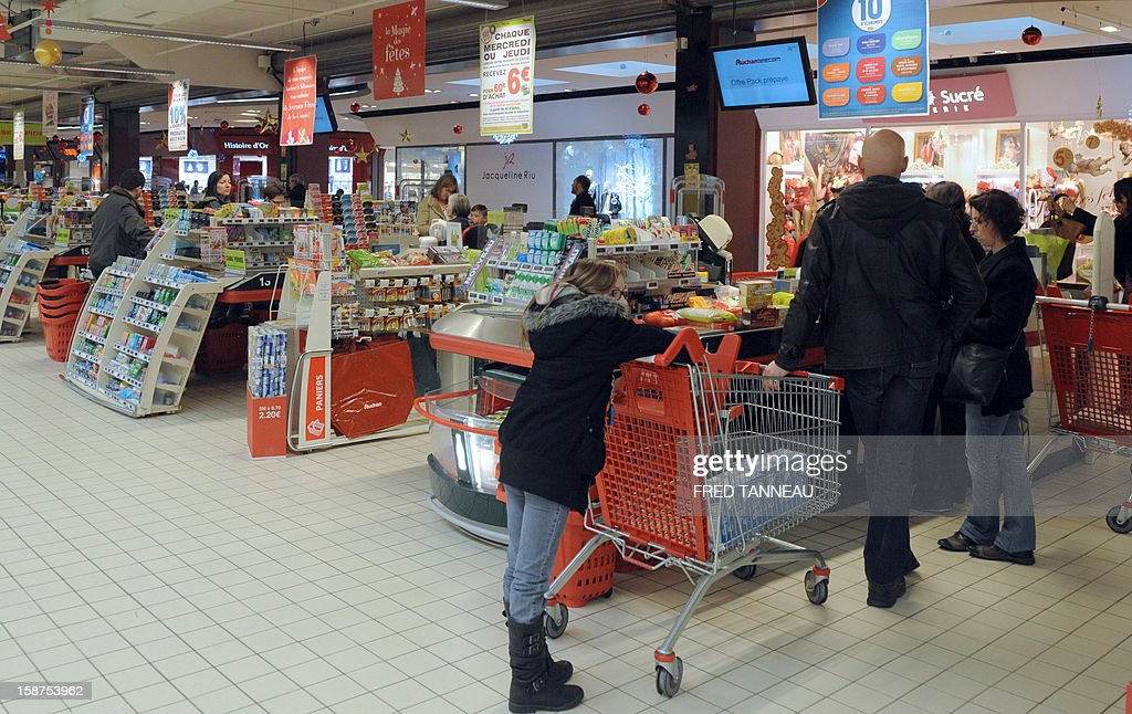 People do their shopping in a supermarket Auchan on December 27, 2012 in Saint-Sebastien-sur-Loire, western France.