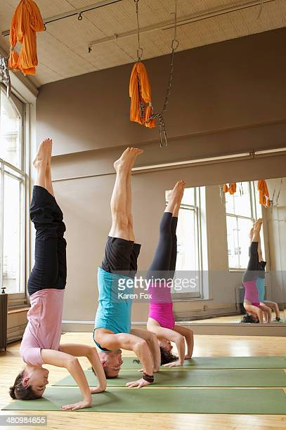 People doing headstands (Salamba-Shirshasana) in yoga class