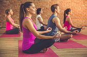 Side view of beautiful sports people sitting in lotus position while doing yoga in modern fitness hall