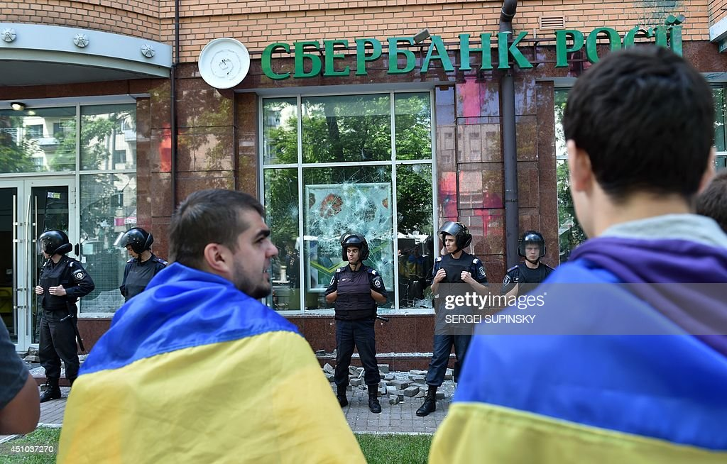 People draped in Ukrainian flags stand in front of policemen guarding the Sberbank of Russia building after it was attacked with stones by activists of various pro-Ukrainian radical youth groups in Kiev on June 22, 2014.