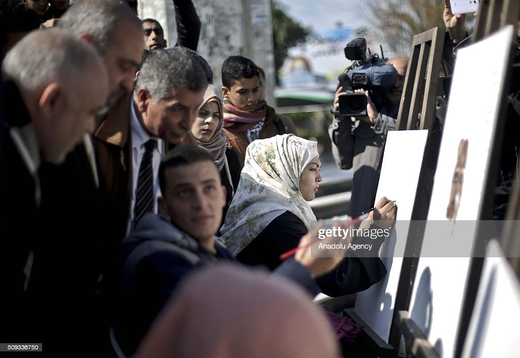 People draw pictures during a protest to demand the release of Palestinian journalist Mohammed al-Qiq who stages a hunger strike in Israeli prison, at Monument of the Unknown Soldier in Gaza City, Gaza on February 10, 2016.