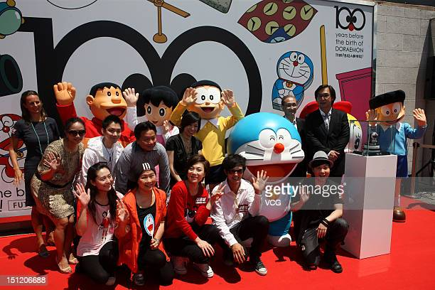 People dreessed as Kouta Takeshi Minamoto Sizuka Nobi Nobita and Honegawa Suneo pose for photos at a celebration on '100 years before the birth of...