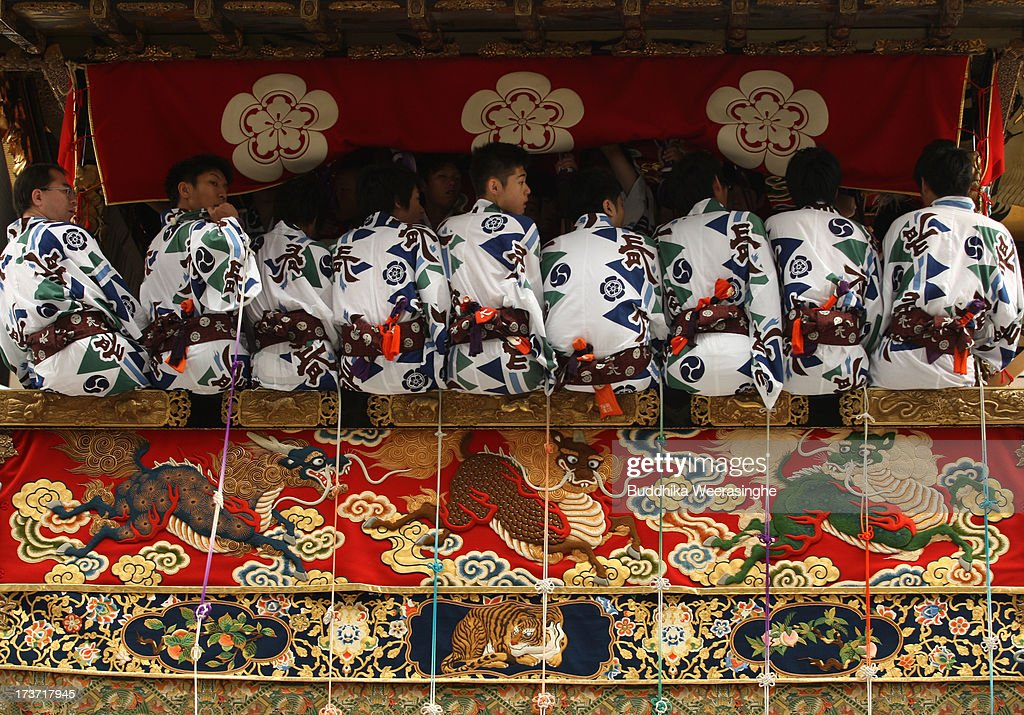 People dress traditional costume as sit inside the float named Yamahoko during the annual Kyoto Gion Festival on July 17, 2013 in Kyoto, Japan. The Gion festival is one of three biggest Japanese festivals. dating back to the 9th century, the festival is part of a ritual intended to satisfy the Gods that brought on fire, floods and earthquakes. During the festival the streets are decorated with lanterns and many of the women dress in 'yukata', summer kimonos.