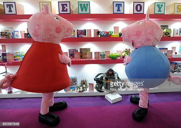 People dressed as cartoon characters Peppa Pig and her brother George look at the best new toys display during the press preview for Toy Fair 2017 at...